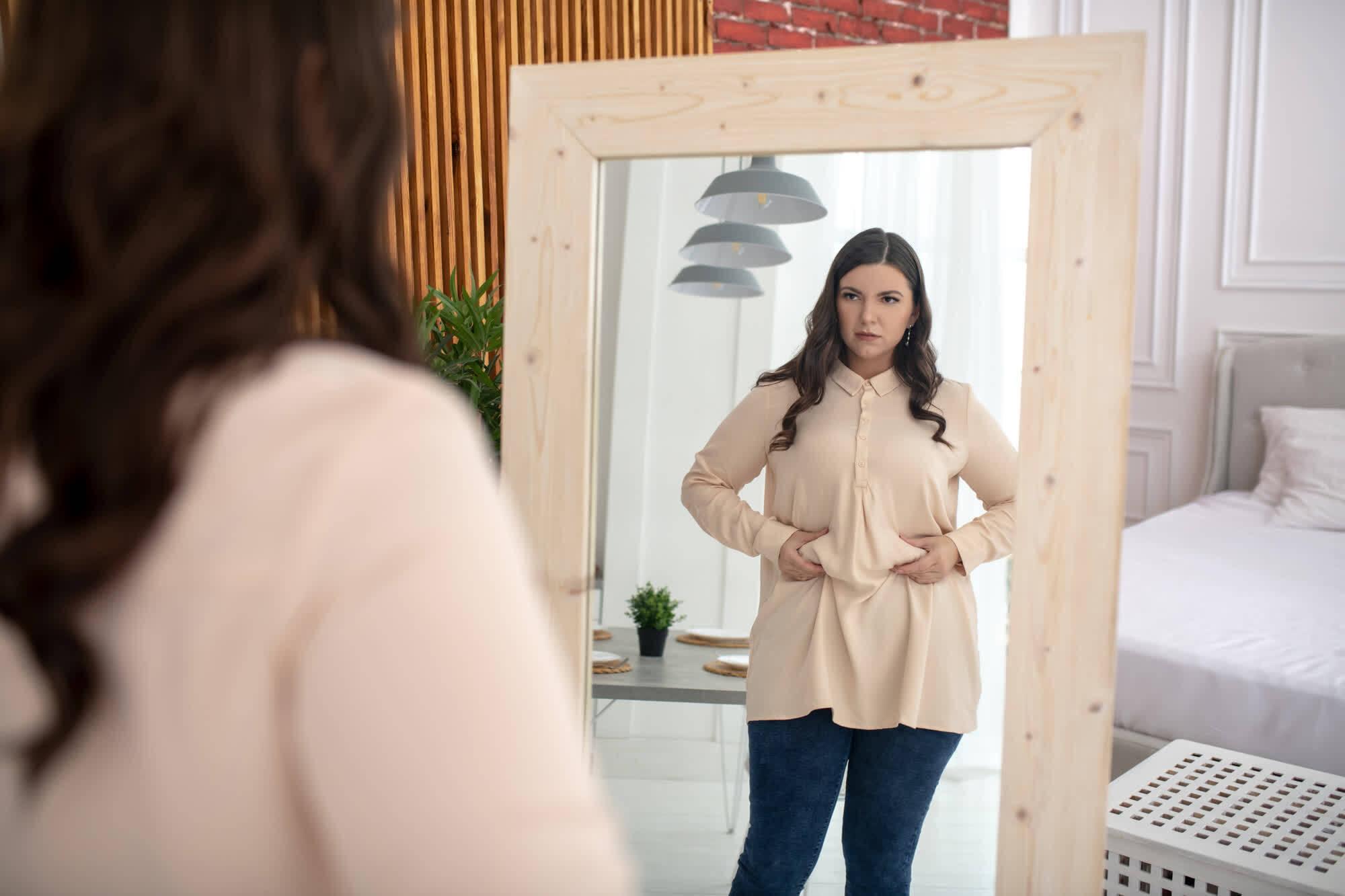 женщина перед зеркалом решает надолго похудеть